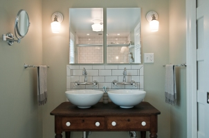 Porcelain vessel sinks sit atop a customized, reclaimed vanity
